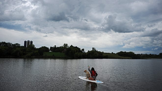 """April Kelling, of Brandon, S.D., takes advantage of a calm Friday afternoon Friday, Sept. 9, 2016, stand up paddle boarding around Lake Alvin with her dog Tre southeast of Sioux Falls. """"It's 70 degrees and no wind,"""" said Kelling adding calm weather was ideal for stand up paddle boarding."""