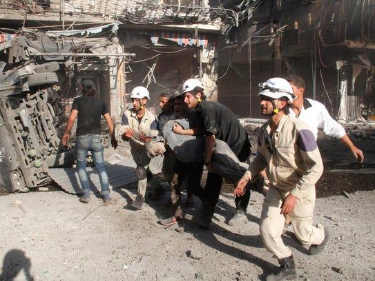 Syrian Civil Defense volunteers rescue a man in Aleppo,