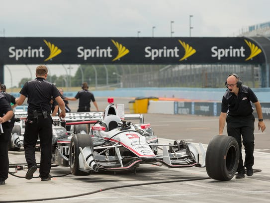Helio Castroneves' car is prepared for the resumption
