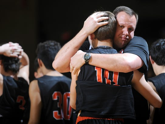 Nocona basketball head coach Bret Botard hugs Marcus
