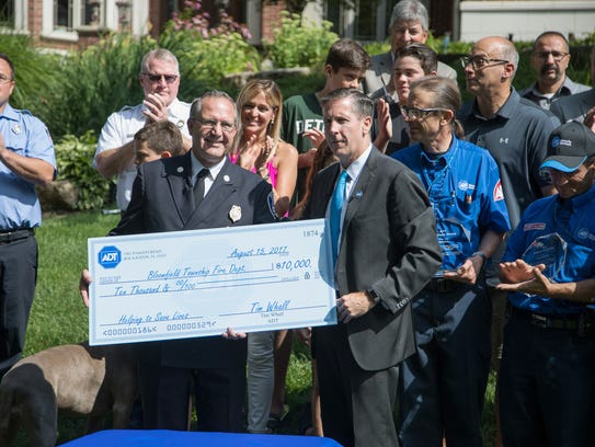 ADT Security CEO Tim Whall, right, presents a $10,000