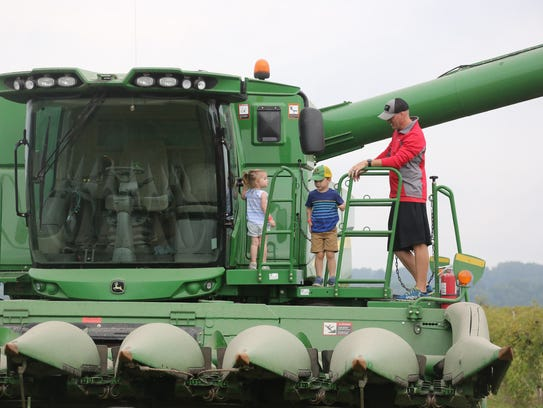 Landry Carpenter, 2, Lincoln Carpenter, 4, and Darrin Carpenter check out a combine at Sandridge Farms in rural Carlisle during the Warren County Farm Tour in August.