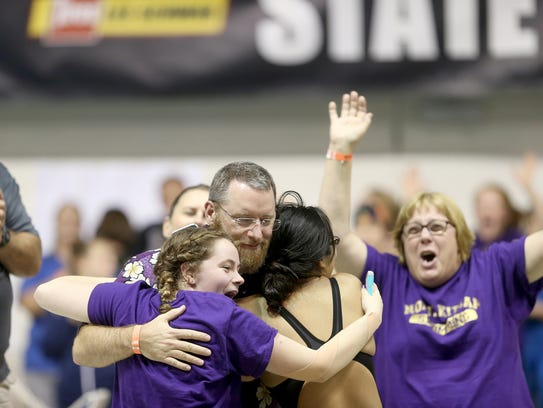 North Kitsap head coach Greg Braun is hugged after being named coach of the meet at the Class 2A state swim championships at the King County Aquatic Center in Federal Way on Saturday.