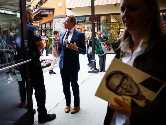 Celebrity stylist Carson Kressley jokes with a security