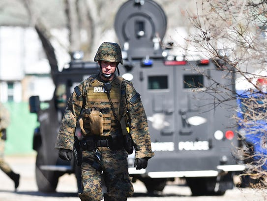 Law enforcement officers search a wooded area for a