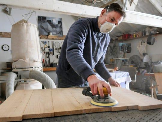 Steve Heymans starts sanding a piece of furniture he