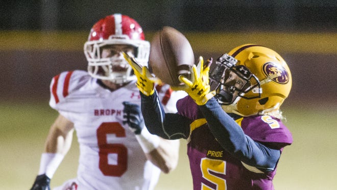 Mountain Pointe High School's Jaydon Brooks, 5, pulls in a pass as Brophy Prep's Noah Pittenger pursues in first quarter action at Mountain Pointe, Friday, November 13, 2015.    #hsfb