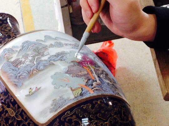 A man hand paints a porcelain vase.