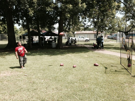 Octavius Lewis, 8, watches after throwing a football toward a target Tuesday during the Rec2U program at Helen Black Park in Alexandria.
