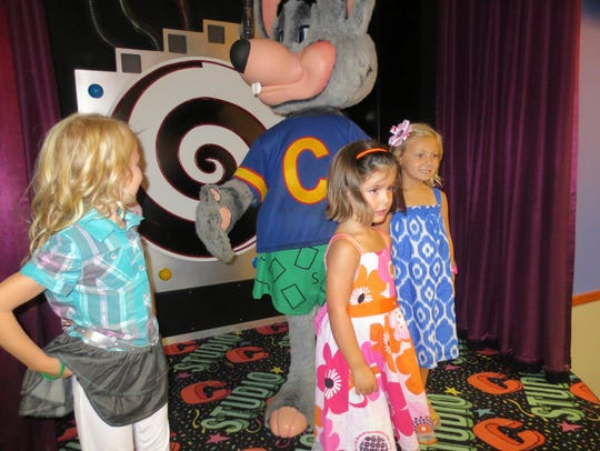 A group of girls pose with Chuck E. Cheese.
