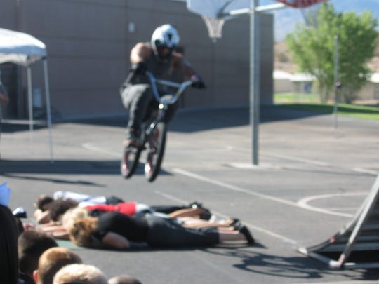 A stuntman jumps over Mr. Rawlins, Mrs. Leavitt, Mrs.