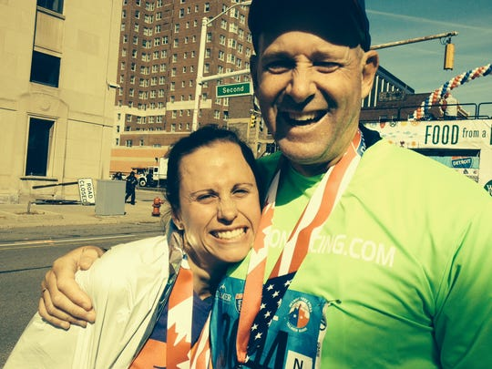 Beth Kline-Markesino gives a big thank-you hug to Gary Morgan of Clarkston after the 2014 Detroit Free Press/Talmer Bank Marathon. Morgan carried  the 6:30 marathon pace sign that gave her the motivation to keep running to the finish line.