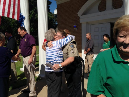 Colfax resident Virginia Foster (right) hugs Grant Parish Sheriff's Cpl. Donna Bryant after a prayer service for law enforcement officers.
