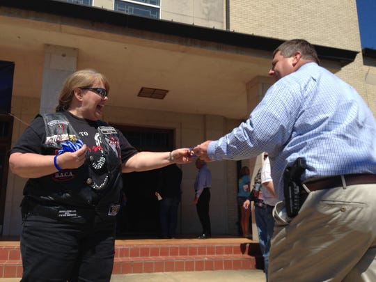 Evelyn Smith, a member of Journey Church, hands a blue wristband to a law enforcement officer on Monday as he enters a prayer service at First Baptist Church in Pineville.