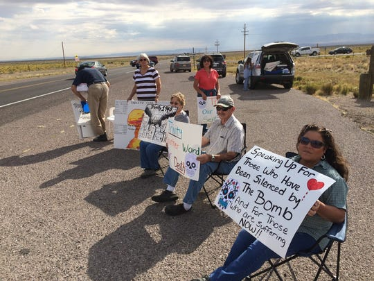 Tina Cordova (red blouse) of the Tularosa Basin Downwinders Consortium and other protesters picket the Trinity Site gate last Saturday.