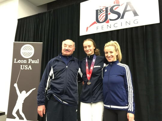 Sofia Komar, a fencer from Old Bridge High School, stands proudly with Coach Yakov and Coach Nastya after winning a silver medal.
