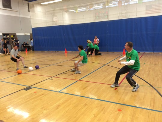 Members of the Johnson County dodgeball team race to