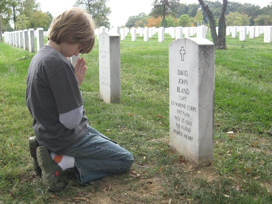 Sawyer Bland kneels at his Marine grandfather's headstone at Arlington National Cemetery.