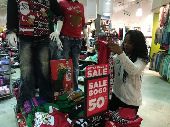 Sheena Hardy prepares a store display at Rue 21 in Governors Square, for Black Friday shopping.