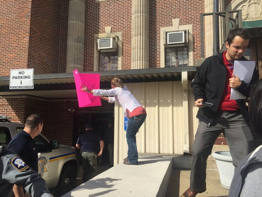 A protester holds a sign as Norris Greenhouse Jr. is whisked into the Avoyelles Parish Courthouse on Tuesday morning.