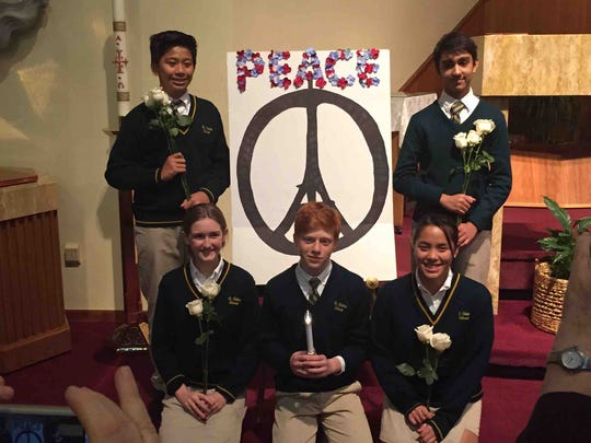 Following the recent terror attacks, in Paris and in California, students at St. Helena's School in Edison conducted a prayer service along with praying a Living Rosary. Pictured are, kneeling, left to right, Madeline Vale, Bret English and Rebecca Penevolpe, and standing, Miguel Zavalla and Akshay Nambiar.
