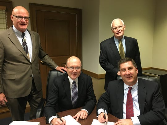 Union State and Baylake bank officials C. Jack Novak, Jeffrey W. Kleiman, Robert W. Agnew, and Robert J. Cera, gathered to sign and finalize their merger Dec. 4.