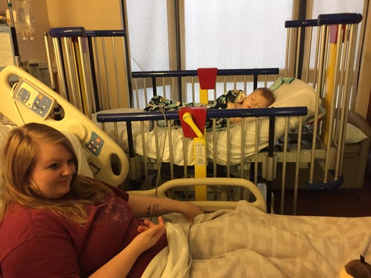 Emily Grahams lies in a hospital bed next to her 11-month-old son, Collin, at Rapides Regional Medical Center's Women's and Children's Hospital on Christmas Eve. Collin was suffering from a respiratory infection, but was resting easier on oxygen.