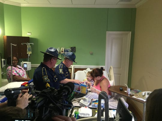 Levi McCall, 1, sits on mother Haylee McCall's lap on Christmas Eve as Louisiana State Police troopres deliver gifts to him.