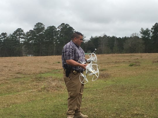 "Grant Parish Deputy James Watkins holds the drone nicknamed ""Jim"" on Monday. The drone was bought by the family of Jim Delaney and the Grant Parish Sheriff's Office after the Delaney family made an offer. Jim Delaney disappeared four years ago and hasn't been seen since."