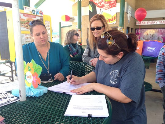 Amanda Pizzuto (right) fills out a form at the Kingsville Sonic in Pineville on Friday. Pizzuto, who is expecting a baby in July, was getting a free child safety seat installed in her vehicle.