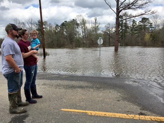 William and Joy Cook, who holds son Matthew, wait for a boat Sunday to check on their flooded home off Highway 500 east of Georgetown in Grant Parish.