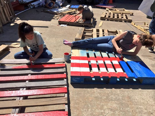 Glenmora High School art students paint Fourth of July designs on wooden pallets Thursday at Sutherlands in Alexandria. The pallets will be sold and proceeds returned to the school's art department.