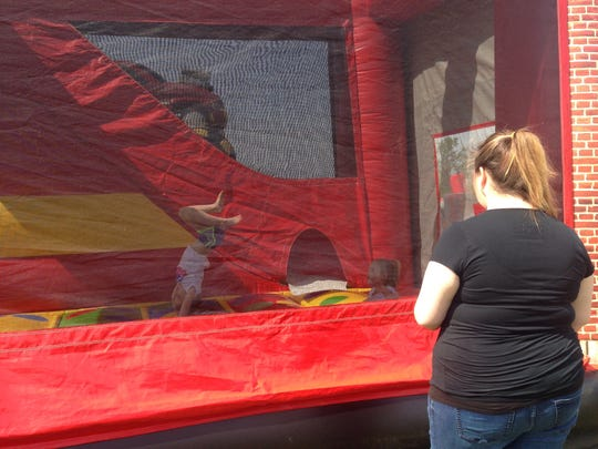 Ashley Kees (right) watches over her 2-year-old daughter, Rosalie Kees (center), as 5-year-old Addison Webster flips in one of the jumpers at the Ruby-Kolin Fire Department's Community Safety Day on Saturday.