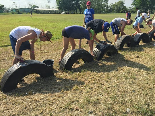 Riverdale IB students scrub tires used for seating at a  soccer field in the community of La Perla in Costa Rica. After washing them, they painted the tires bright colors.