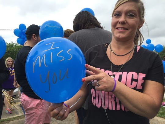 Lace Evans holds a balloon on which she wrote a message