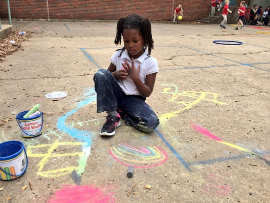 Cherokee Elementary pre-K student Brooklyn Smith takes a moment to reflect on her rainbow drawing in sidewalk chalk Monday during Week of the Young Child activities.