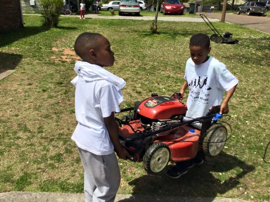 Two boys who volunteer with Raising Men Lawn Care Service help carry a lawnmower to the car.