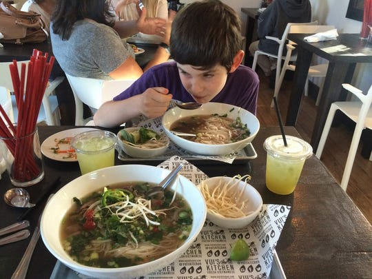 Arthur Myers enjoys a bowl of pho at Vui's Kitchen, which opens next week in Berry Hill.