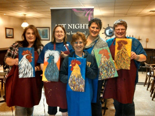 A group of Zander's Art Night students hold up their finished canvas paintings of roosters.