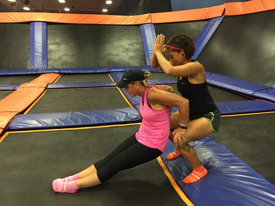 "Kelly Galyeh (in pink) and Devon White, head fitness instructor at Sky Zone in Newark, demonstrate partner exercises on the trampoline. ""It's an addiction,"" Galyeh said."
