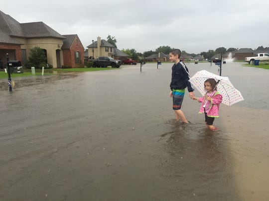 Dylan Fine, 11, crosses a flooded road with his sister Alejandra Blanco, 3, in Sawgrass Subdivision in south Lafayette.