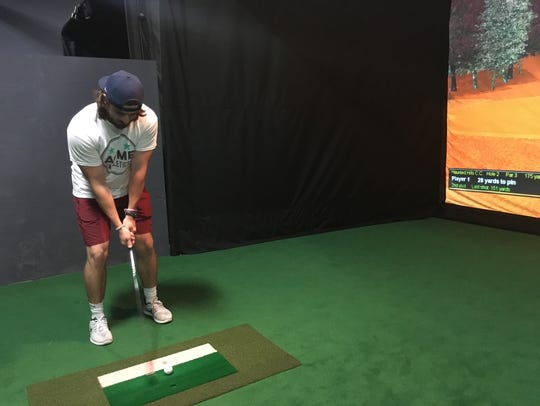 Chase Knott takes a practice swing in the golf simulator.