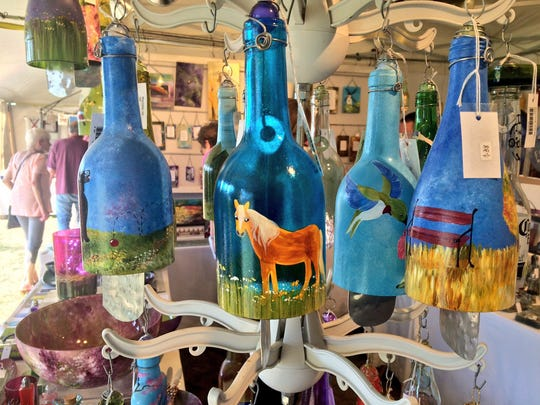 Artist Amalia Flaisher creates whimsical designs on wine bottles recycled as wind chimes. The wind chimes were among many of the unique offerings at the Woodstock/ New Paltz Art and Crafts Fair Sunday.