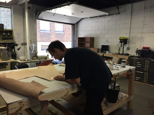 James Lee, 28, of Detroit, works with leather at Douglas & Co., Detroit.