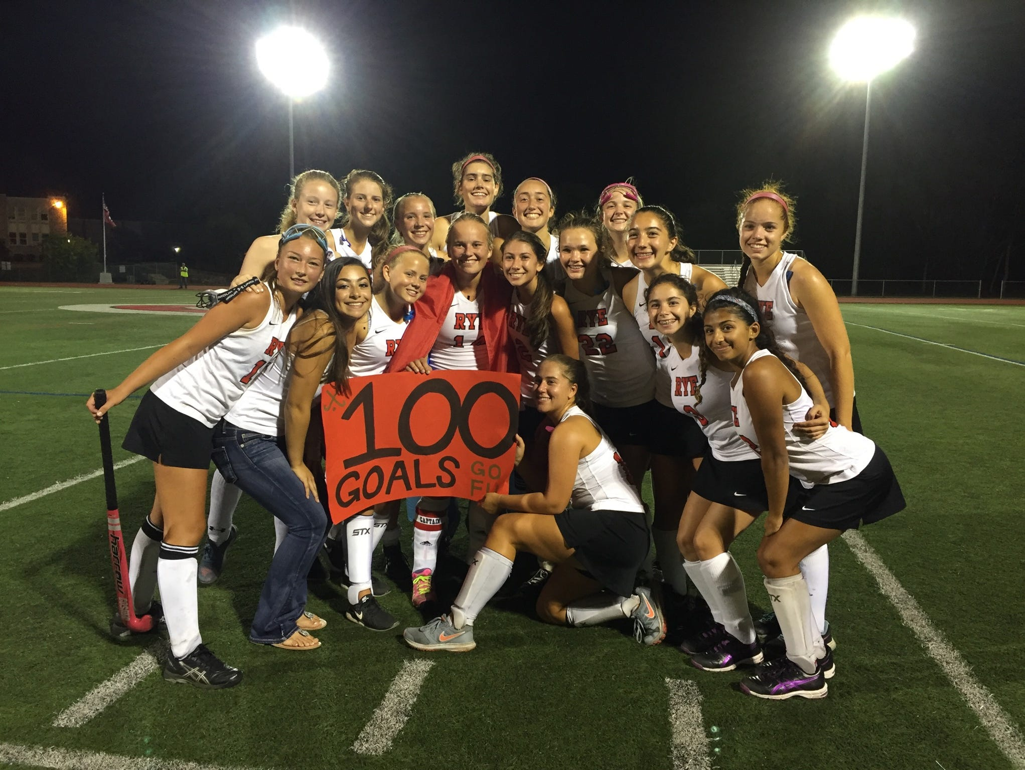 Rye players celebrate teammate Fusine Govaert's (center) 100th career goal Saturday night. Govaert got the milestone with a hat trick against Bronxville..