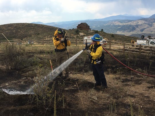 Firefighters douse the remnants of Stag Hollow Fire, which burned 4.7 acres on Milner Mountain west of Fort Collins. Local fire crews responded to more than 130 calls during a summer-long burn ban.