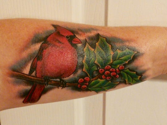 """Old wives tales say when you see a red cardinal, it's the spirit of a loved one coming to visit you,"" Tracy Neudecker Jarrell said of her tattoo. ""That's why I got the red cardinal.""   Jarrell was very close to her father she said. Living next door to her parents, she saw him everyday before he died.  When her father passed away he was cremated, as Jarrell said he donated his body to science.   In order to keep a piece of her father with her at all times, she had a small amount of his ashes added to the ink in her tattoo.  Life, she said, is different without him around, and she will miss the days living next to her father forever.   But mostly, Jarrell said, she will miss the days on the farm together, ""sitting on the tailgate of his truck 'solving all the world's problems', as he put it."""