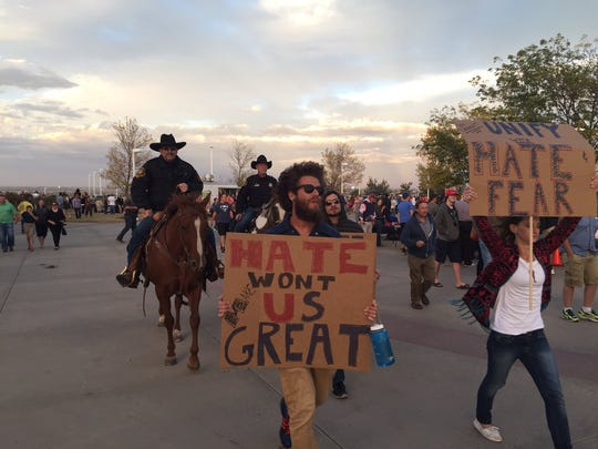Protesters are escorted away from the lawn area at the Budweiser Events Center on Monday during the Donald Trump rally.