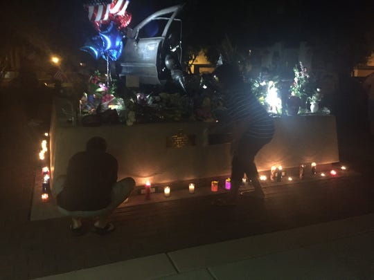 Mourners arrange votive candles around a memorial outside Palm Springs Police Department headquarters.