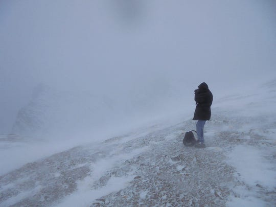 Alex Blake braces against 40 mph winds at the top of Siyeh Pass in Glacier National Park on Friday.